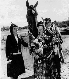 Macdougal gets a touch of the tartan and a swirl of the bagpipes, 1959, just prior to his Melbourne Cup win